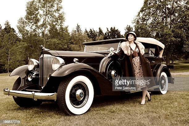 Caucasian woman by vintage car