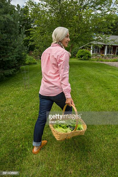 Caucasian woman carrying basket of vegetables in backyard