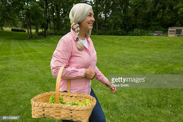 Caucasian woman carrying basket of vegetables in garden