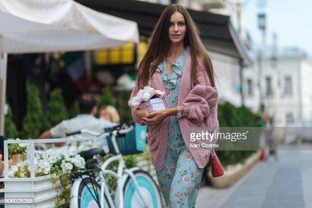 Caucasian woman carrying gift box near bicycle