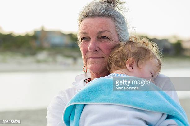 Caucasian woman carrying grandson on beach
