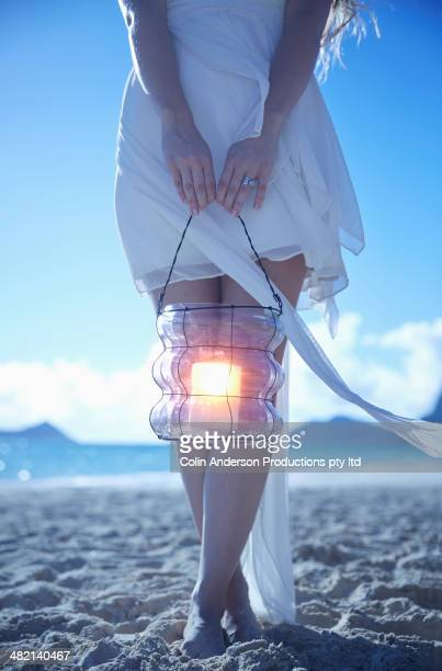Caucasian woman carrying lantern on beach