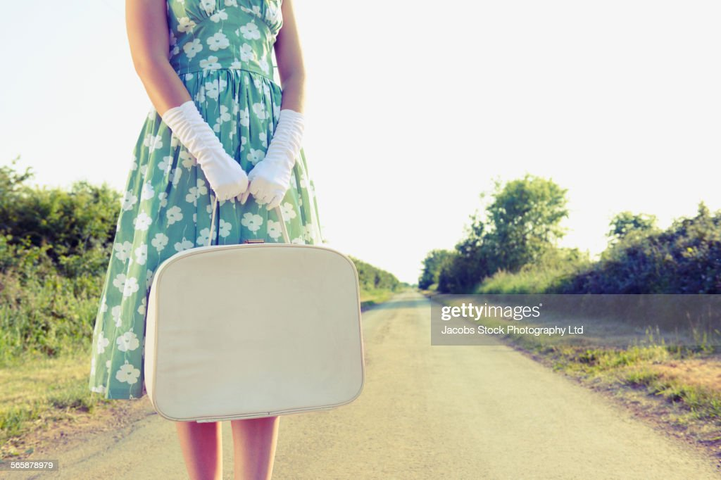 Caucasian woman carrying luggage on rural road : Stock Photo
