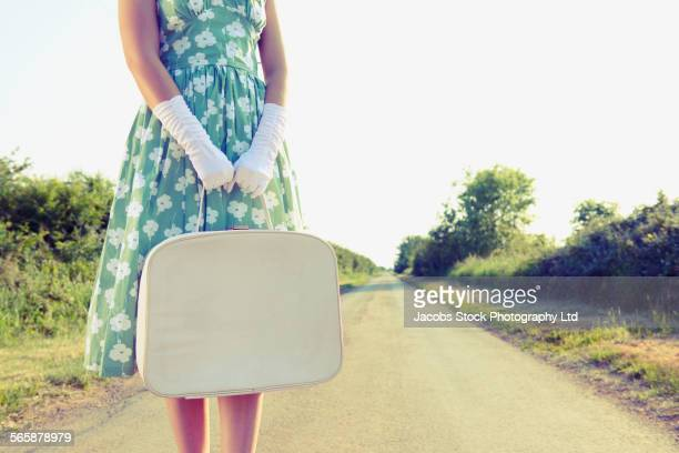 Caucasian woman carrying luggage on rural road