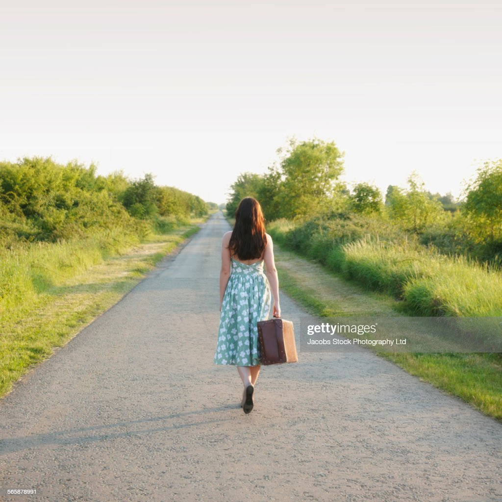 Caucasian woman carrying suitcase on rural road : Stock Photo