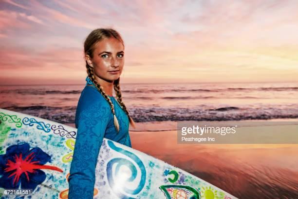caucasian woman carrying surfboard at beach - blond frauen strand stock-fotos und bilder
