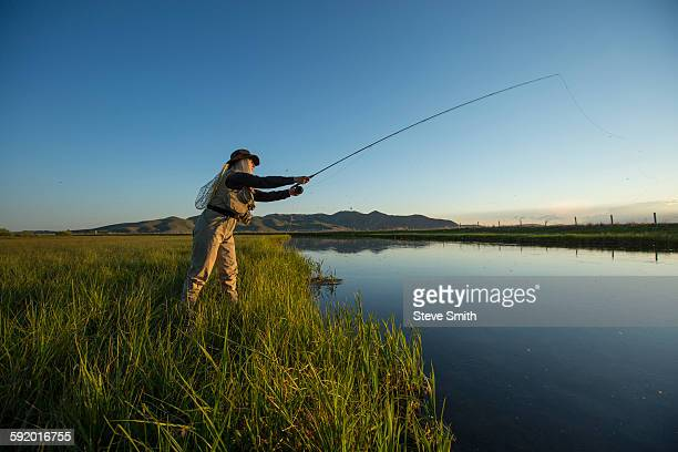 caucasian woman casting fishing line in remote lake - sun valley idaho stock photos and pictures