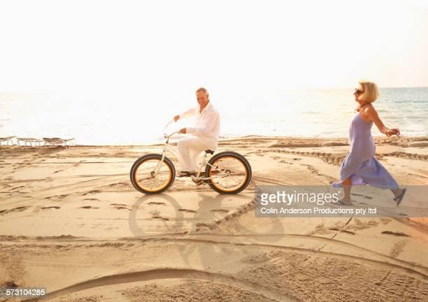 Caucasian woman chasing husband riding bicycle on beach