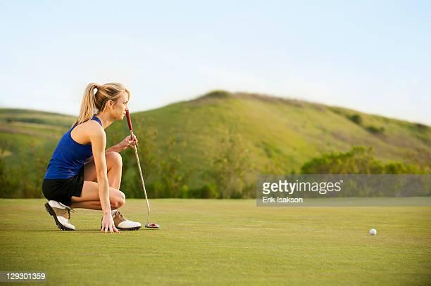 caucasian woman checking ground on golf course - einlochen golf stock-fotos und bilder