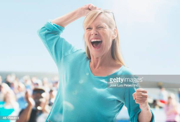 Caucasian woman cheering at sporting event