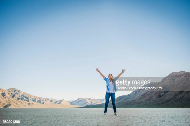 Caucasian woman cheering in cracked desert landscape