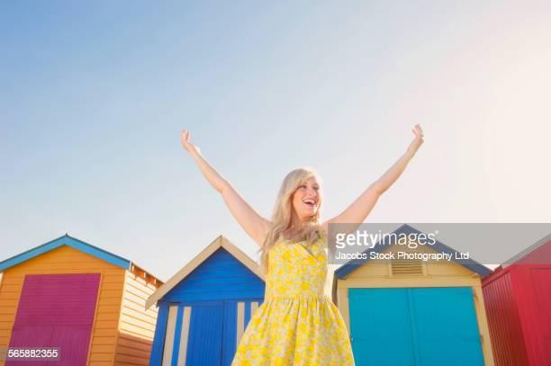 Caucasian woman cheering near colorful beach huts