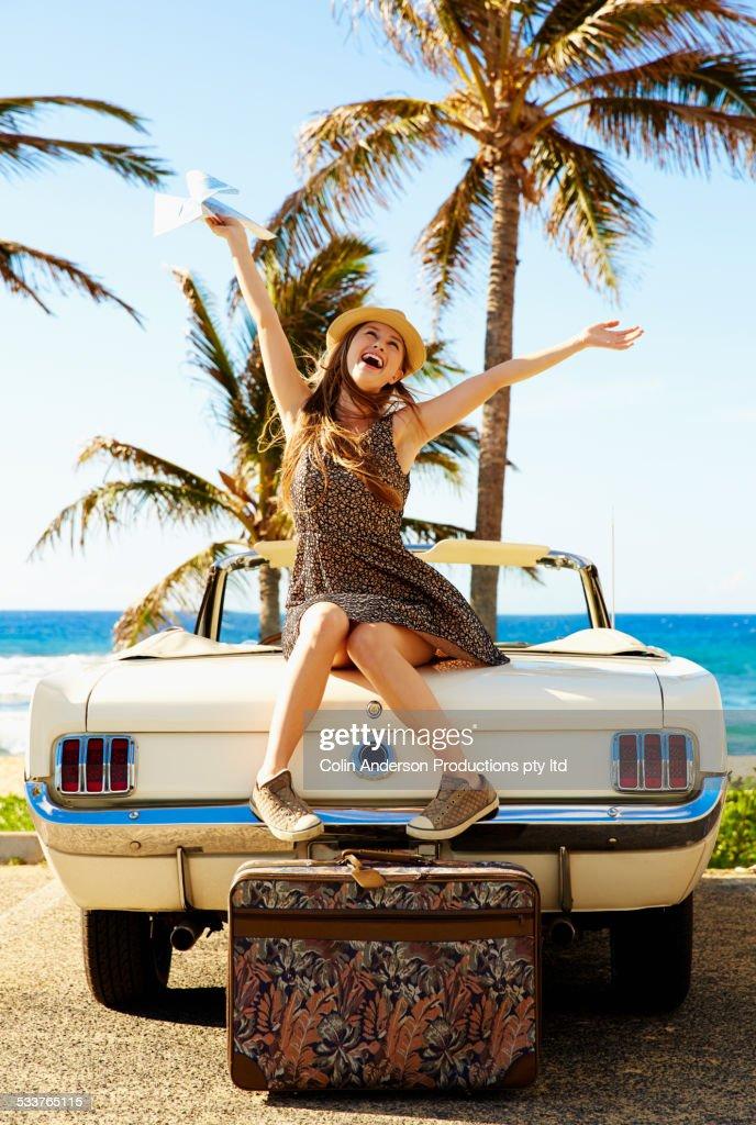 Caucasian woman cheering on convertible on beach : Foto stock