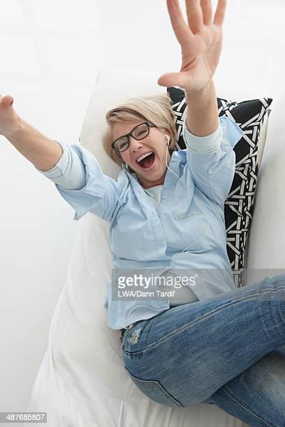 Caucasian woman cheering on sofa