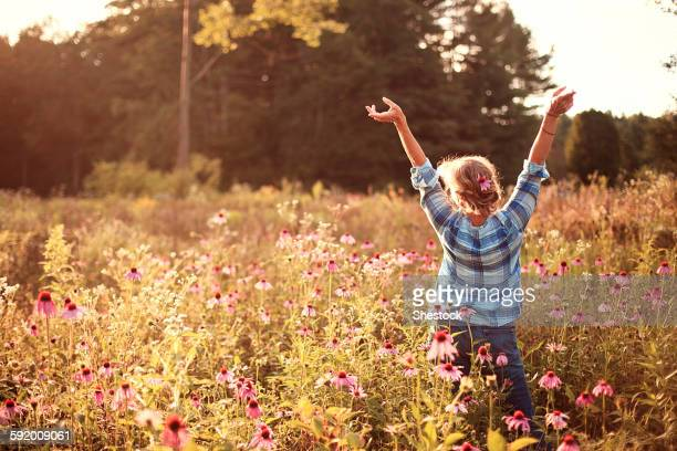 Caucasian woman cheering with arms outstretched in field