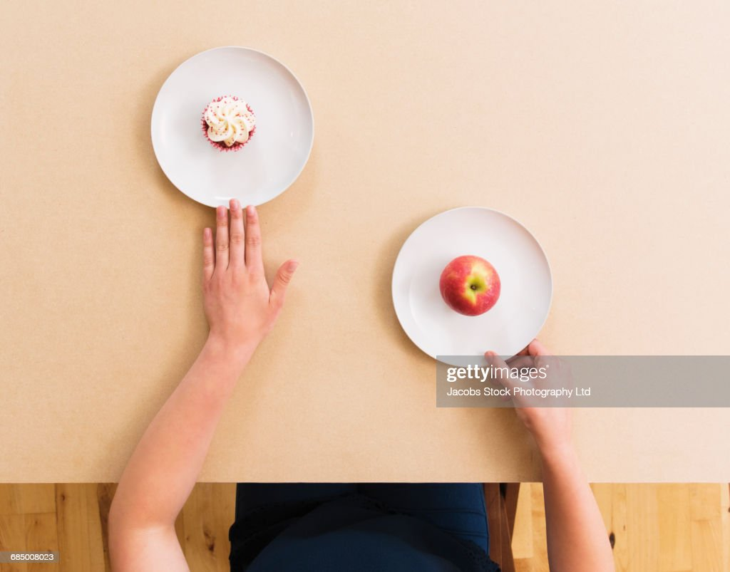 Caucasian woman choosing apple instead of cupcake at table : Stock Photo