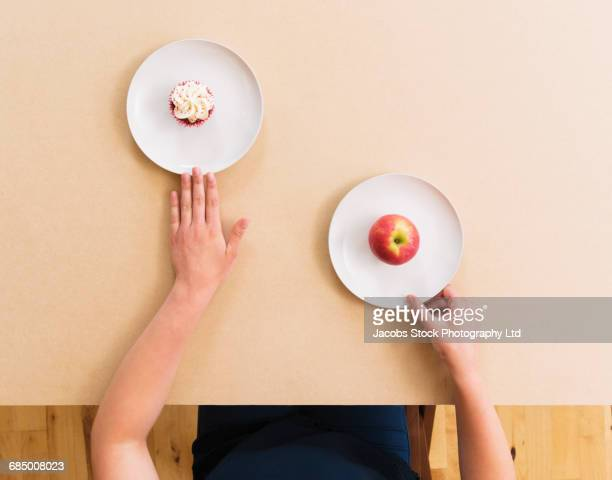 Caucasian woman choosing apple instead of cupcake at table