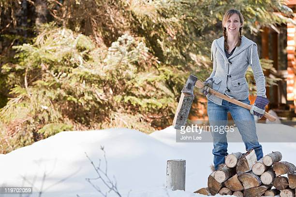 Caucasian woman chopping firewood in snow