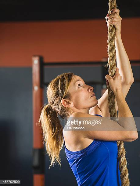 Caucasian woman climbing rope in gym