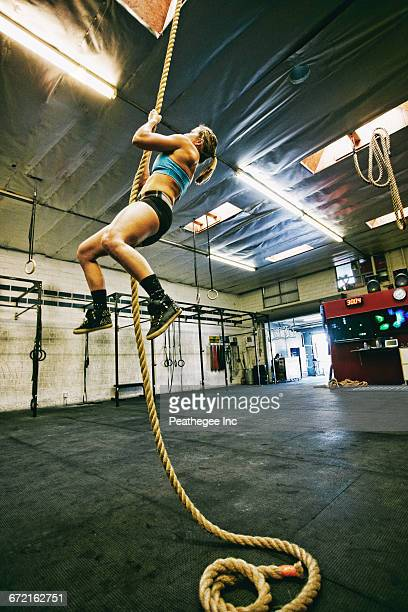 Caucasian woman climbing rope in gymnasium