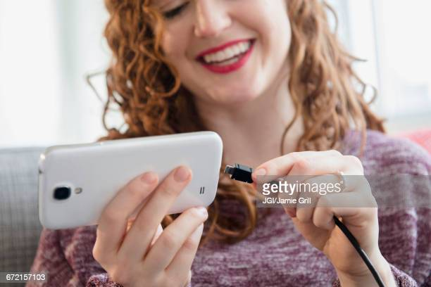 caucasian woman connecting cord to cell phone - electrical component stock photos and pictures