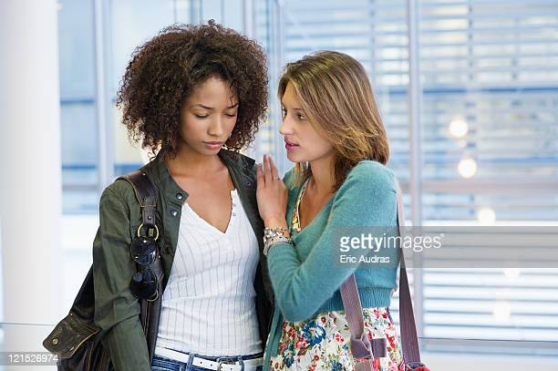Caucasian woman consoling to an African American woman in university