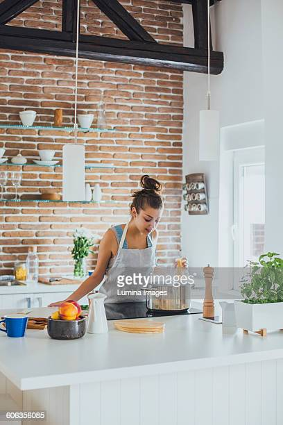 Caucasian woman cooking in kitchen
