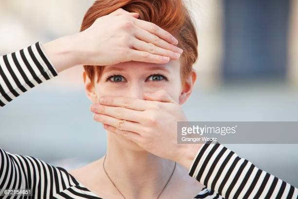 Caucasian woman covering mouth and forehead with hands