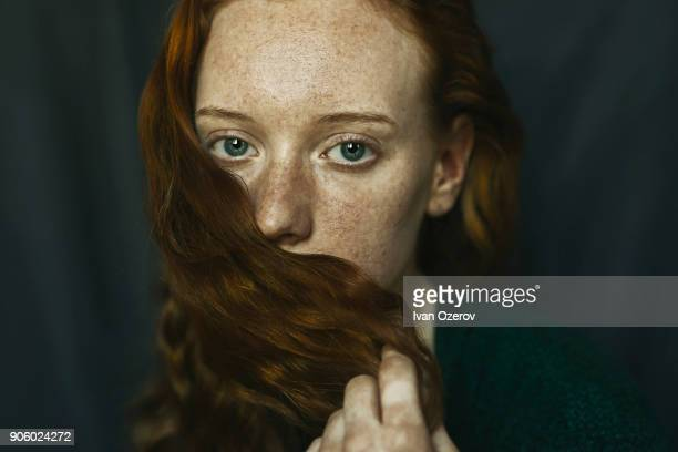 caucasian woman covering mouth with hair - verlegen stockfoto's en -beelden
