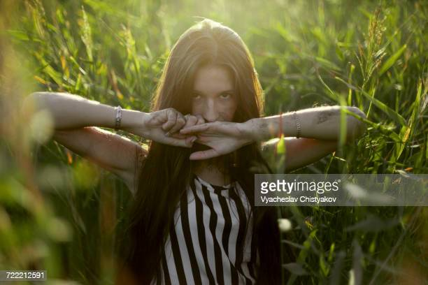 Caucasian woman covering mouth with hands in field