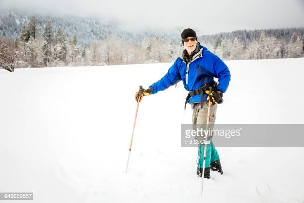 Caucasian woman cross-country skiing in snowy field