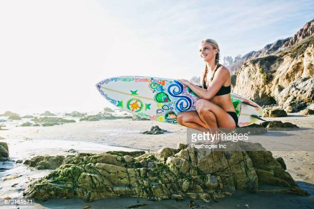 Caucasian woman crouching on rock carrying surfboard at beach