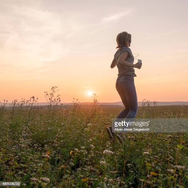 Caucasian woman dancing in field at sunset