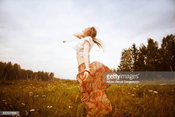 Caucasian woman dancing in field