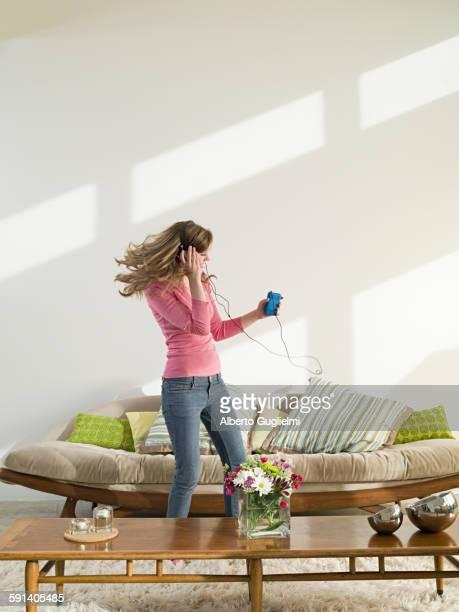 Caucasian woman dancing to headphones in living room
