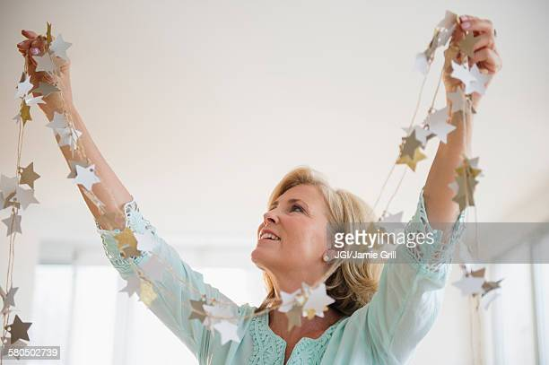 caucasian woman decorating with garland in living room - garland decoration stock pictures, royalty-free photos & images