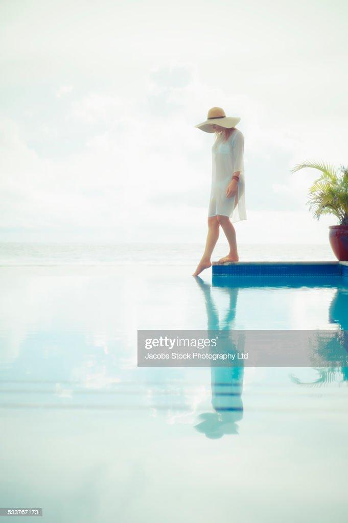Caucasian woman dipping toe in swimming pool : Foto stock