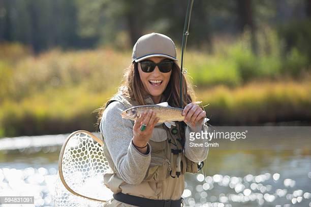 Caucasian woman displaying fishing catch