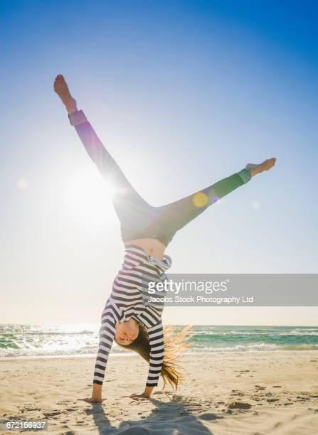 Caucasian woman doing cartwheel on beach