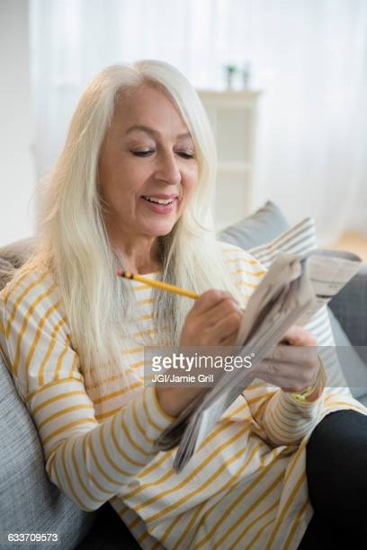 Caucasian woman doing crossword puzzle