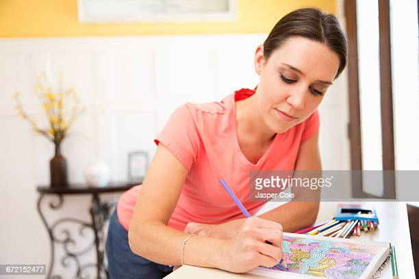 caucasian woman drawing in coloring book - colouring book stock photos and pictures