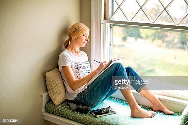 Caucasian woman drawing in windowsill