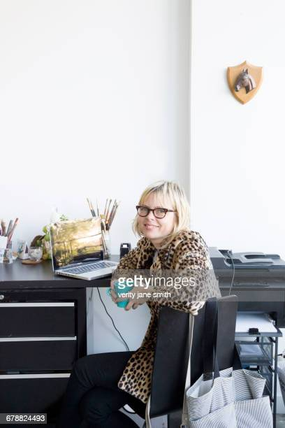 Caucasian woman drinking coffee at desk with laptop