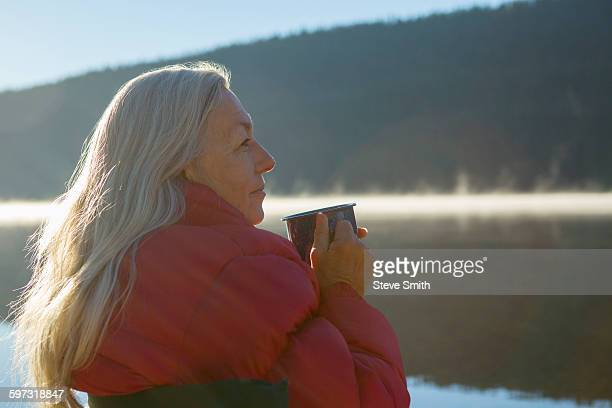 Caucasian woman drinking coffee at lake