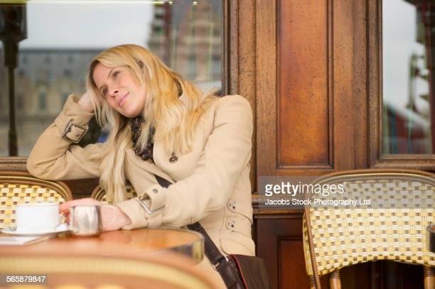 Caucasian woman drinking coffee at sidewalk cafe