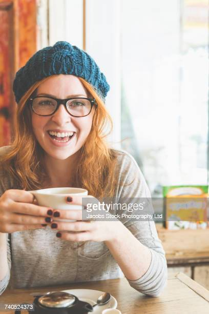caucasian woman drinking coffee in coffee shop - one young woman only stock pictures, royalty-free photos & images
