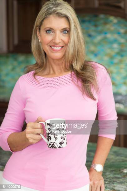 Caucasian woman drinking coffee in kitchen