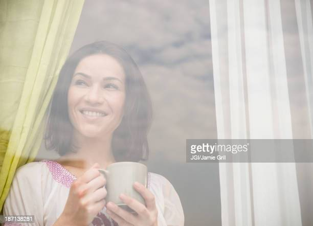 Caucasian woman drinking cup of coffee by window