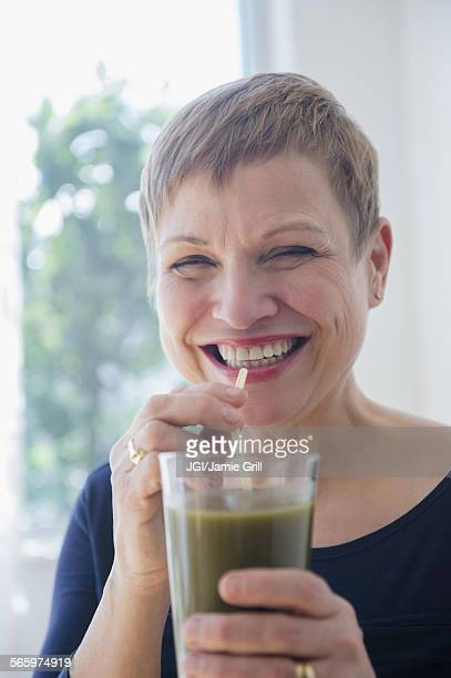 Caucasian woman drinking glass of healthy juice