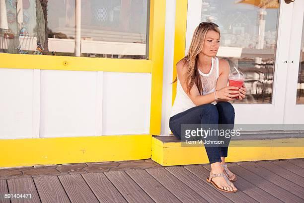 Caucasian woman drinking juice outside restaurant